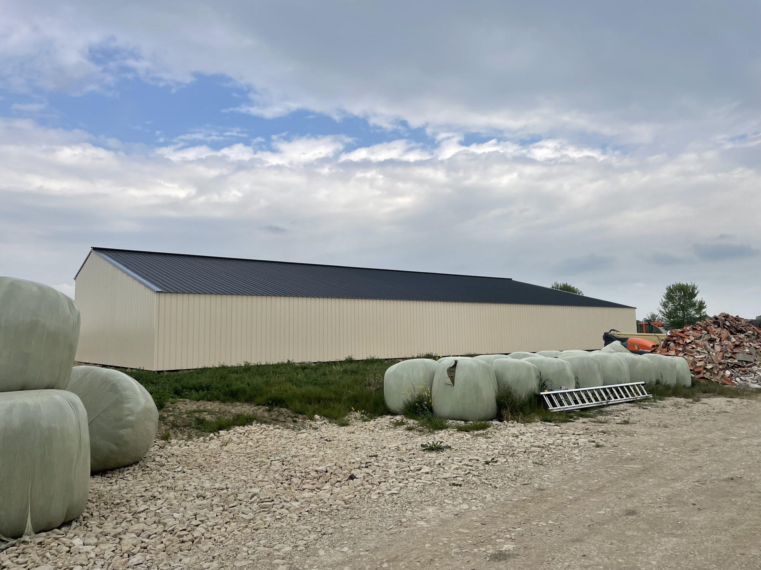 Hangars neuf avec panneaux solaires sur le toit et des bottes de pailles devants