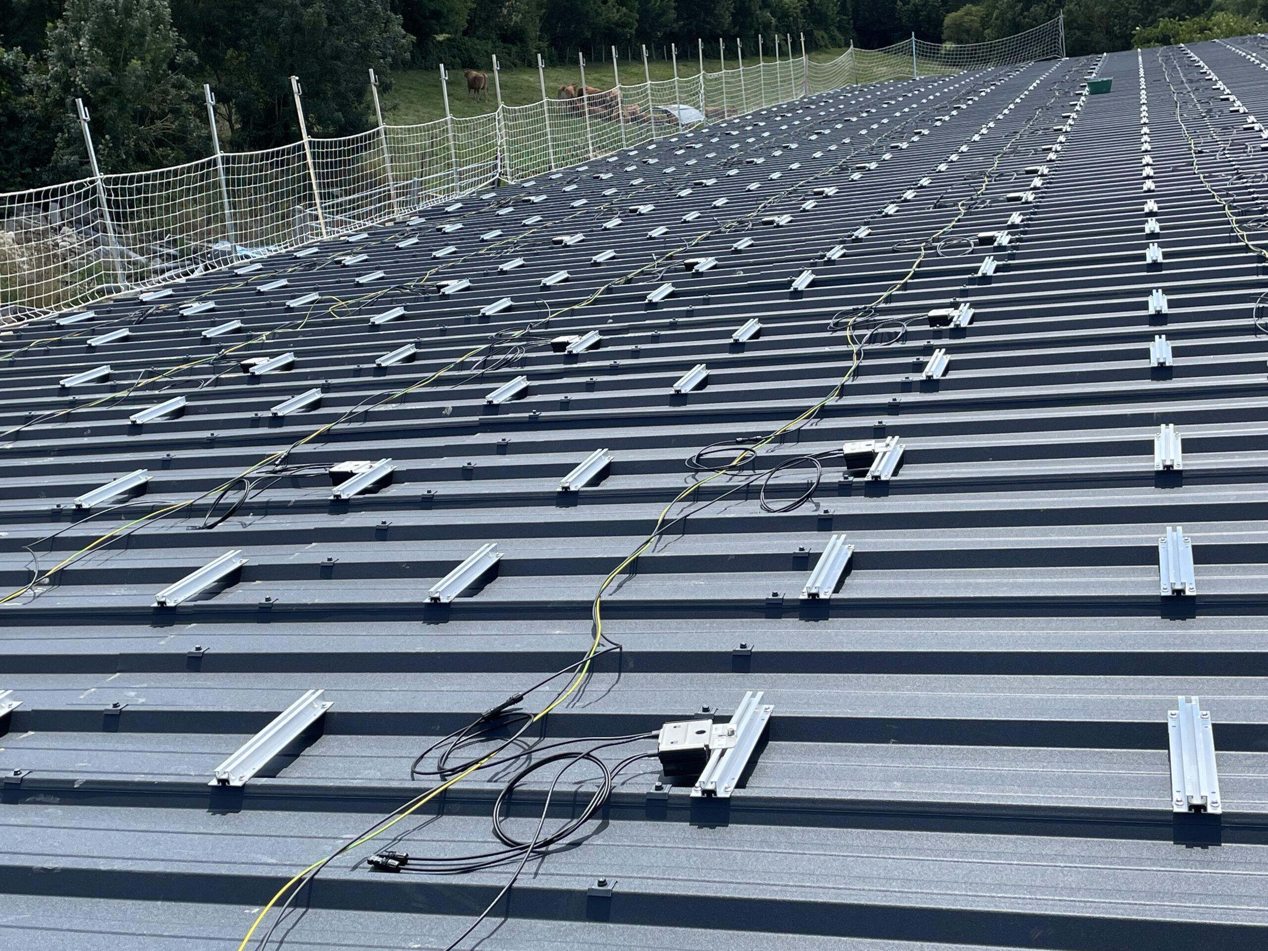 Fixation avant panneaux solaires sur le toit d'un hangar